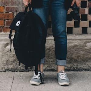 Teen Holding Backpack