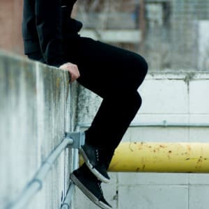 Teen Sitting on Low Wall